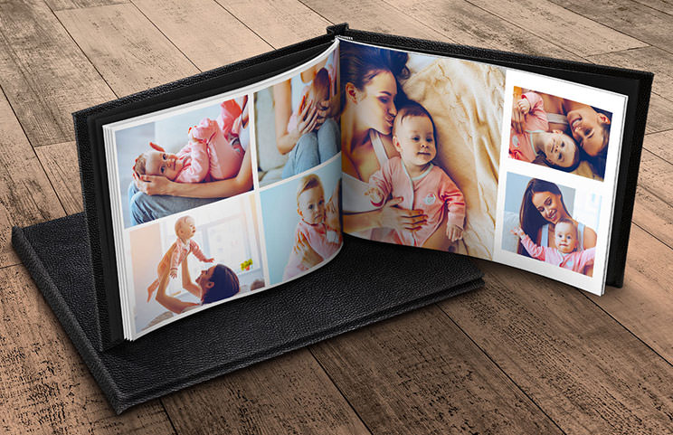 Custom made photo album open on table with photo collage of family photos