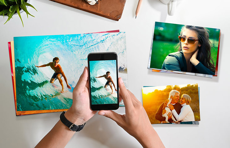 Small medium and large photo prints on table from mobile phone