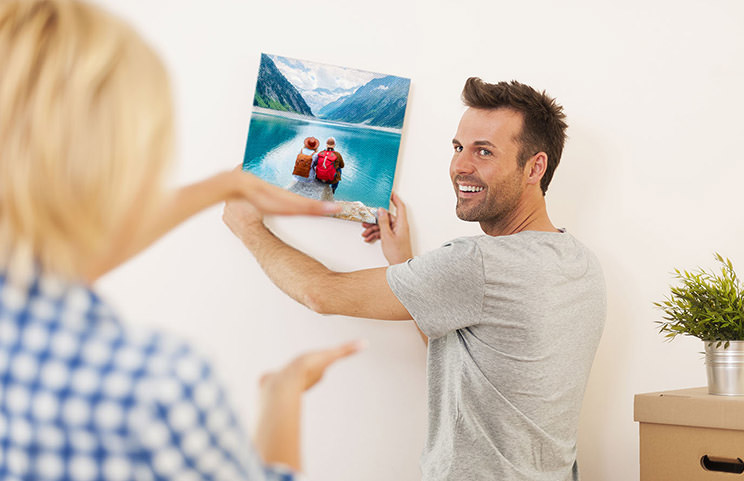 Man and woman putting up a photo canvas with a holiday photo on
