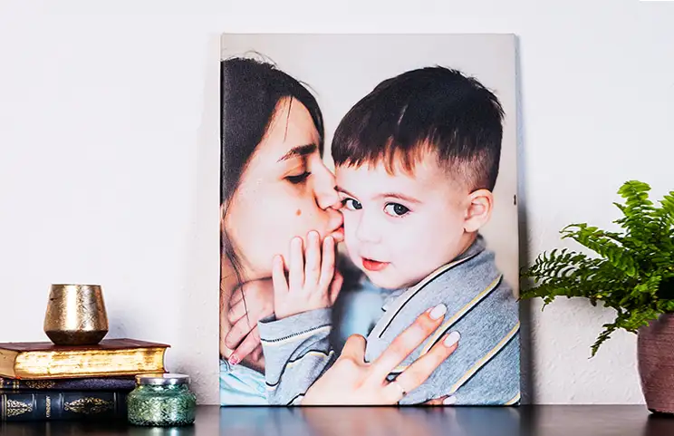 Young woman placing Printerpix custom photo canvas with photo of baby and dog on wall