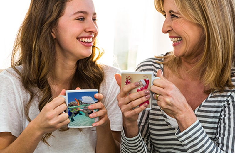 Mum and daughter holding custom designed photo mugs with family photos