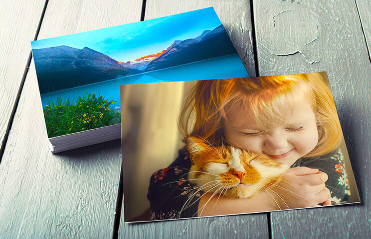 Stack of family photo prints of girl and cat from photo printing service