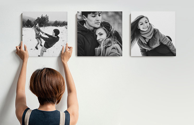 Woman putting up three black and white family photo canvases