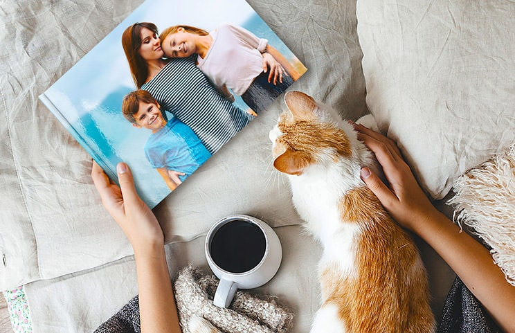 Pet and woman looking at personalised family photo book with custom design