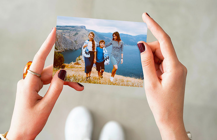Hands holding a photo print of three kids on holiday