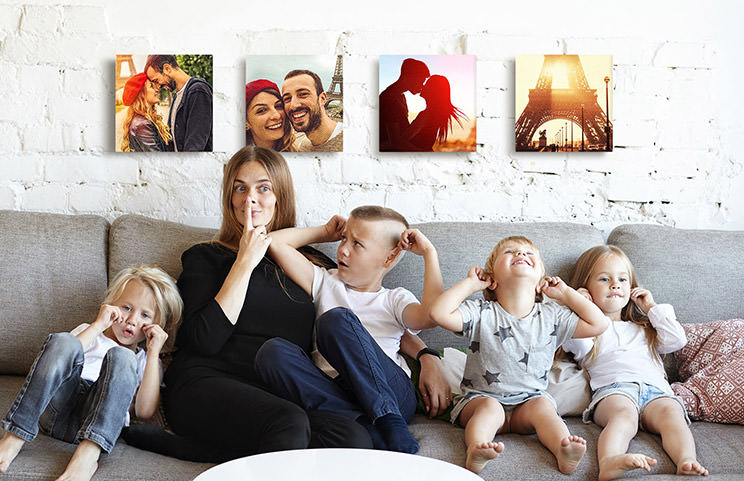 Mom and four young kids sitting on sofa in front of four photo canvases