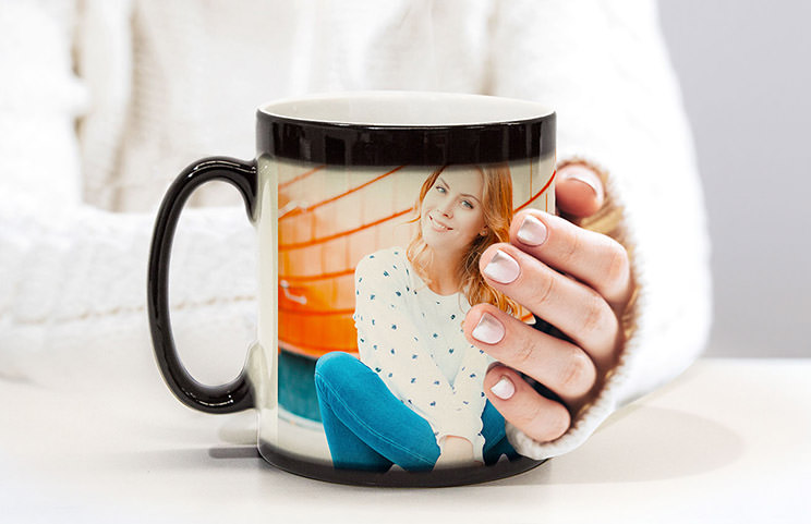 Couple holding two heat changing magic mugs with custom text by Printerpix