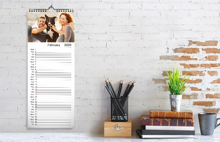 Woman looking at customised calendar with photo of dog taken on mobile